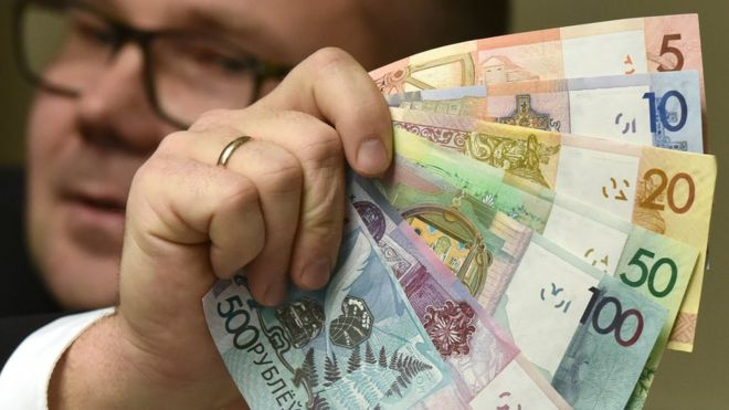 A man holding the new denominations of banknotes