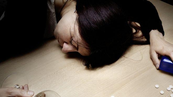 Drogadicta dormida sobre una mesa