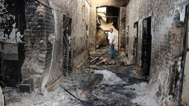 An employee of Doctors Without Borders stands inside the charred remains of their hospital after it was hit by a US airstrike in Kunduz