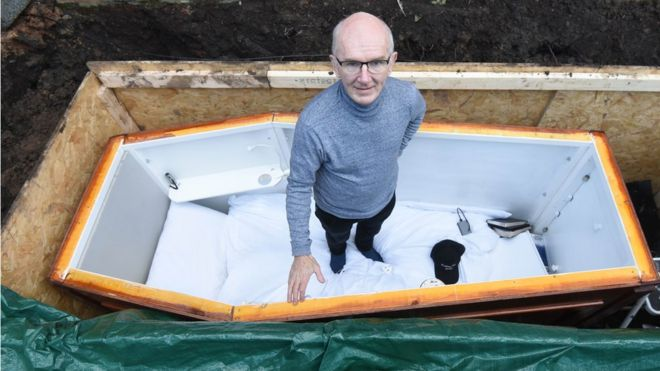 John Edwards posando en el ataúd antes de ser enterrado.