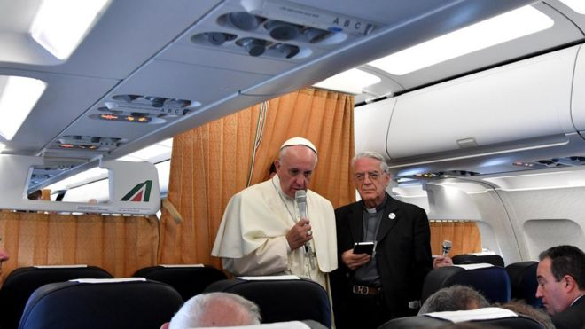 Pope Francis, flanked by Vatican spokesman Federico Lombardi, talks to journalists on flight back to Vatican, at end of three-day visit to Armenia, Sunday, June 26