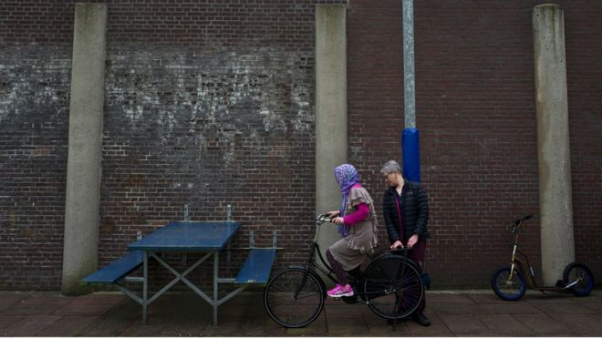 A Dutch volunteer teaches an Afghan refugee woman how to ride a bicycle