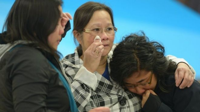 A mother (centre) is greeted by her daughters after arriving in Edmonton from the Fort McMurray area. Photo: 5 May 2016