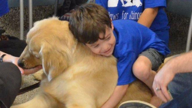 Niño abrazando a un perro.