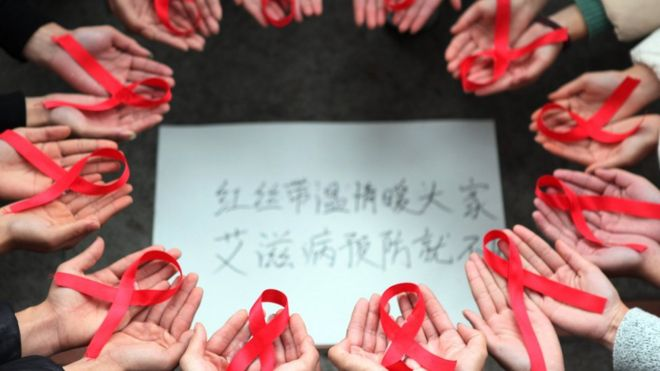 This picture taken on 30 November 2015 shows volunteers holding red ribbons above a piece of paper written in Chinese that reads ''Red ribbons bring warmth to everyone to prevent AIDS' during an event for World Aids Day in Chongqing