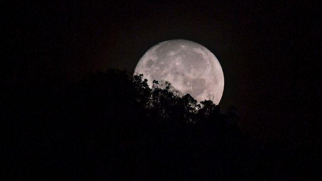 La Luna detrás de una colina arbolada