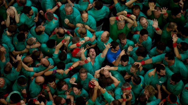 """Members of the """"Castellers de Villafranca"""" react after completing their human tower during the 26th Human Tower Competition in Tarragona, Spain, on Sunday, Oct. 2, 2016."""