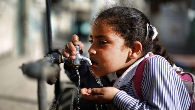 Niña tomando agua de una canilla en Gaza
