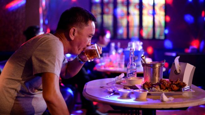 A customer drinks beer at a night club in Davao City