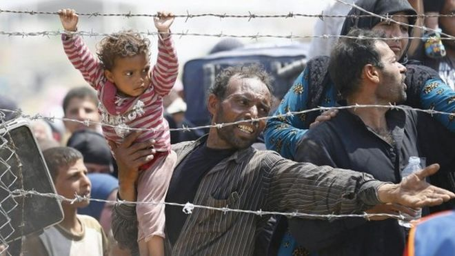 A Syrian refugee holds onto his daughter as he waits to cross into Turkey