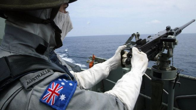 A member of he Royal Australian Navy mans his machinegun during an exercise in the South China Sea
