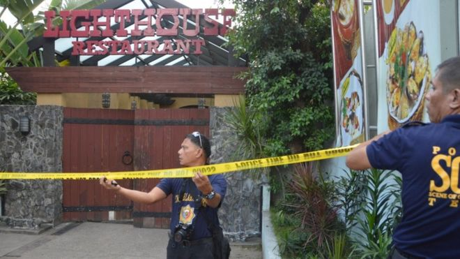 Police mark the crime scene with a yellow tape where two Chinese diplomats were killed in Cebu province, central Philippines on Wednesday Oct. 21, 2015.