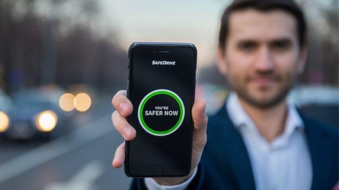 Tudor Cobalas holding phone showing SafeDrive app