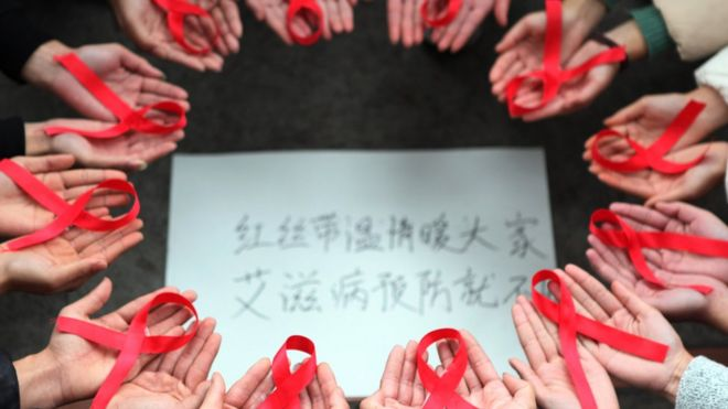 Voluntarios en china con cintas rojas