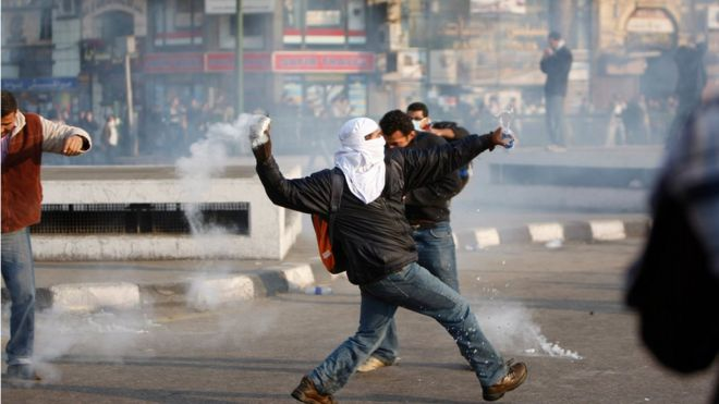 A protester throws back a tear gas canister toward police at a demonstration in Cairo, Egypt Tuesday, Jan. 25, 201