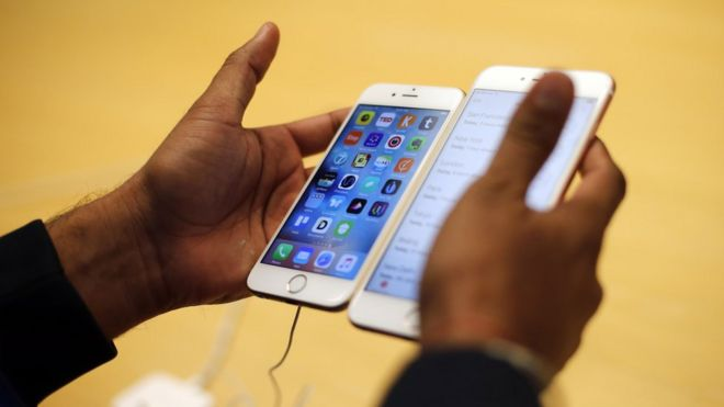 Man holding two new iPhones