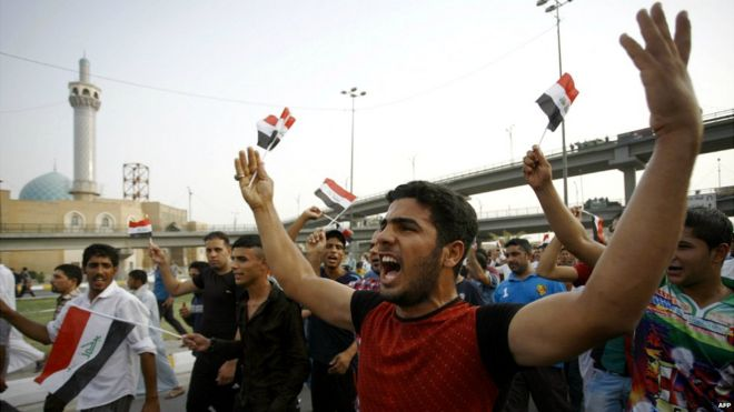 Iraqi men shout slogans and wave flags during a demonstration against corruption and poor services in Najaf - 7 August 2015
