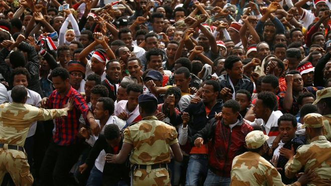 Demonstrators chant slogans while flashing the Oromo protest gesture during Irreecha in Ethiopia - 5 October 2016