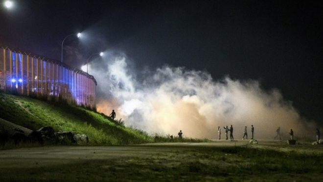 Migrants clash with French riot police as they attack the fence next to the makeshift Jungle camp in Calais (22 October 2016)