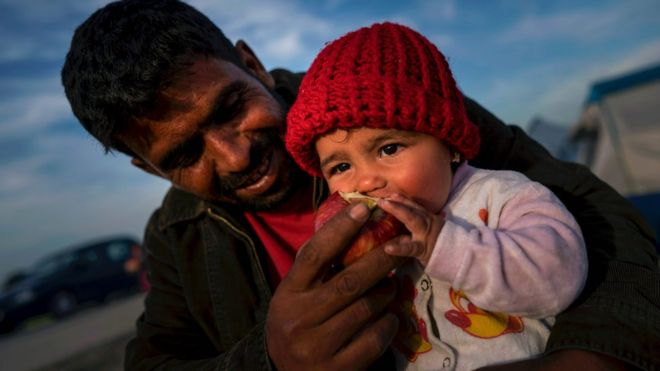A refugee feeds his baby with an apple at sunset at a makeshift camp for migrants and refugees at the Greek-Macedonian border near the village of Idomeni on 27 April 2016