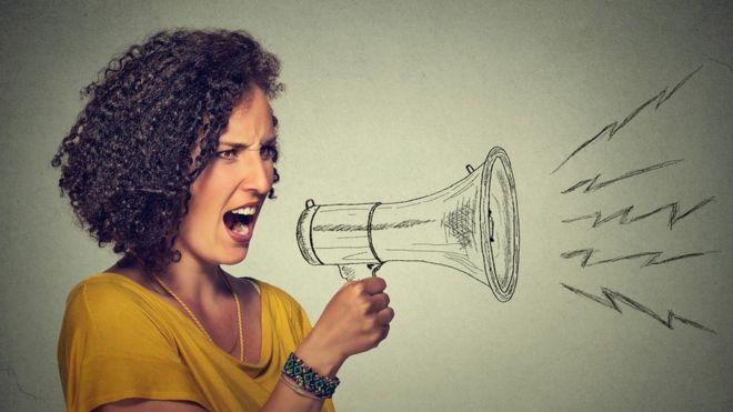 Una mujer gritando por el dibujo de un megáfono, enfurecida