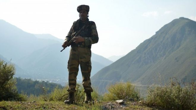An Indian army soldier stands guard near the site of a gun battle between Indian army soldiers and rebels inside an army brigade headquarters near the border with Pakistan, known as the Line of Control (LoC), in Uri on September 18, 2016.