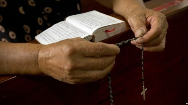 A Christian woman reads a bible at a church in Zhejiang, China (30 July 2015)