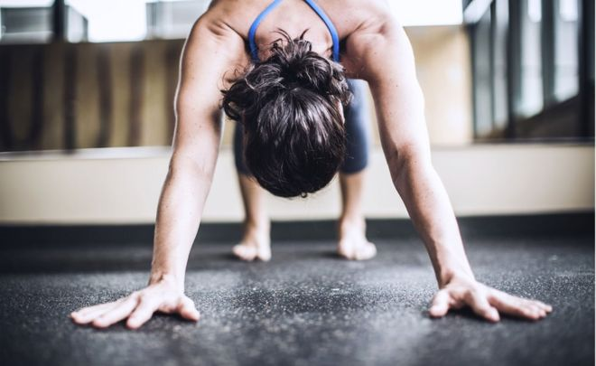 A woman in a downward-facing dog yoga position