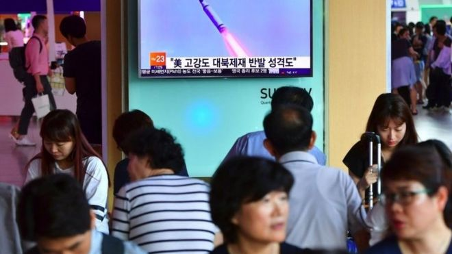 People watch a television news broadcast at a railway station in Seoul on July 9, 2016, showing file footage of a North Korean missile launch. North Korea on July 9