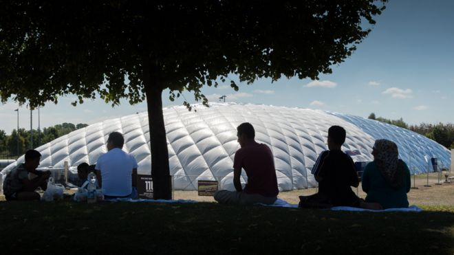 A family sits beneath a tree in front of an air dome currently serving as a refugee accommodation in Taufkirchen, Germany, 05 August 2015.