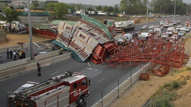The collapsed bridge lies across the highway, blocking traffic