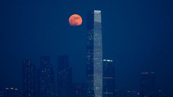 The moon rises over Victoria Harbour in Hong Kong, Monday, Nov. 14, 2016