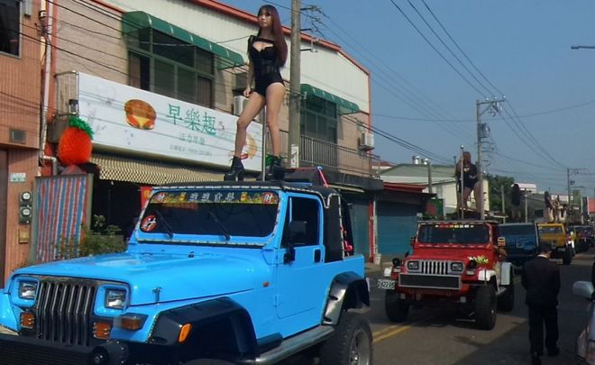 This picture taken on 3 January 2017 shows pole dancers performing on top of jeeps during the funeral procession of former Chiayi City county council speaker Tung Hsiang in Chiayi City, southern Taiwan
