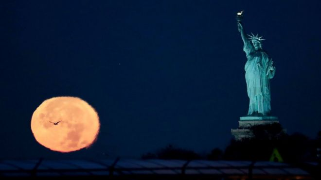 The supermoon appears near the Statue of Liberty, Monday, Nov. 14, 2016, in New Yor