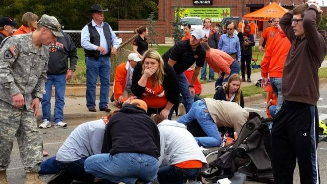 Bystanders help the injured after a vehicle crashed into a crowd of spectators during the Oklahoma State University homecoming parade (24 October 2015)