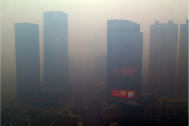 This picture taken on 8 November 2015 shows a residential block covered in smog in Shenyang, China's Liaoning province