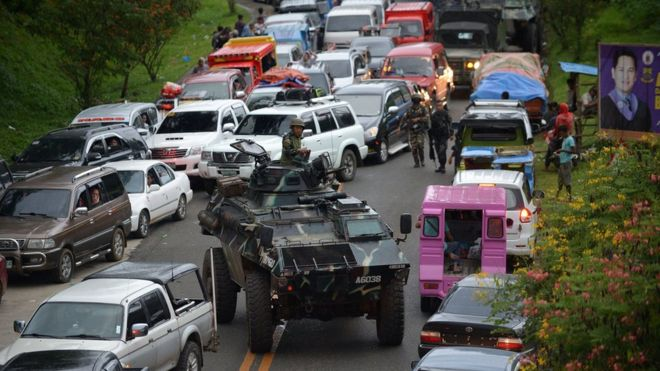 An armoured personnel carrier moves amongst stuck vehicles of residents fleeing Marawi City, in the southern island of Mindanao