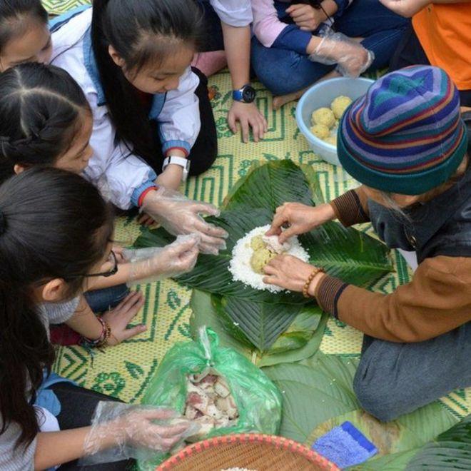 Trẻ em Việt Nam học cách gói bánh chưng Tết tại Bảo tàng Dân tộc học, Hà Nội