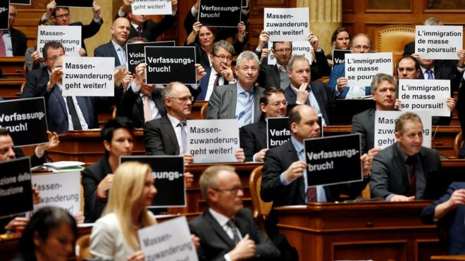 """Deputies from the Swiss People's Party hold posters reading """"constitutional breach"""" and """"mass immigration continues"""" after the vote on giving Swiss jobseekers priority in parliament in Bern, Switzerland on 16 December 2016"""