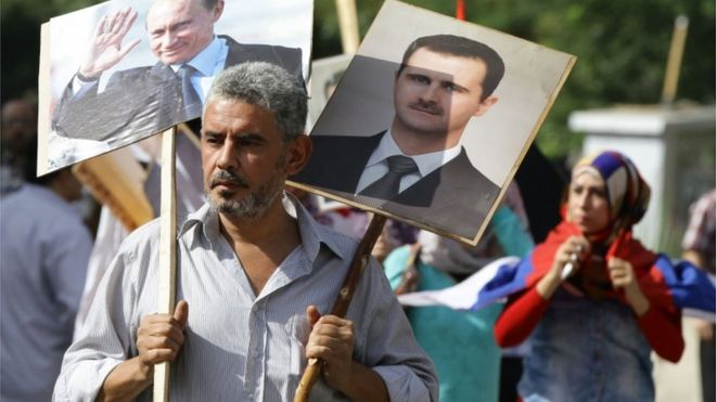 A Syrian man holding up portraits of President Bashar al-Assad and his Russian counterpart Valdimir Putin (L) joins several hundred people who gathered near the Russian embassy in Damascus to express their support for Moscow's air war in Syria
