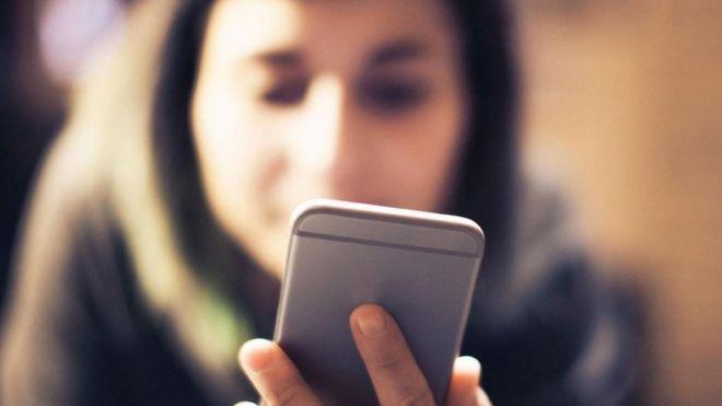 Una joven viendo su teléfono inteligente