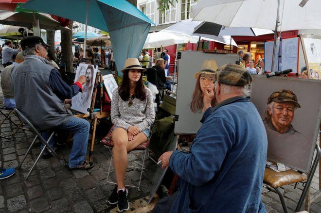 Un artista pinta un retrato de una joven turista cerca de la iglesia del Sagrado Corazón en Montmartre, París.