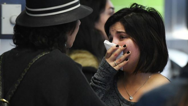 A woman of Iranian descent (R) cries as she waits for a family member after the immigration ban