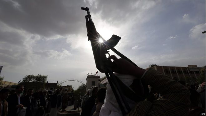 An armed Houthi supporter holds up guns during a protest
