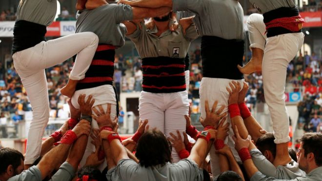 """Castellers de Sants start to form a human tower called """"castell"""" during a biannual competition in Tarragona city, Spain, October 2, 2016."""