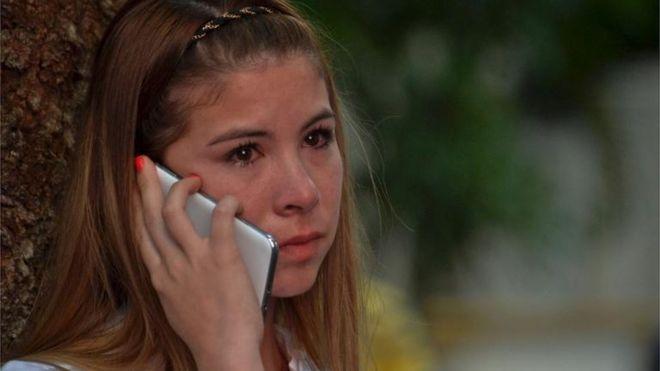 Una joven habla por teléfono con los ojos enrojecidos.