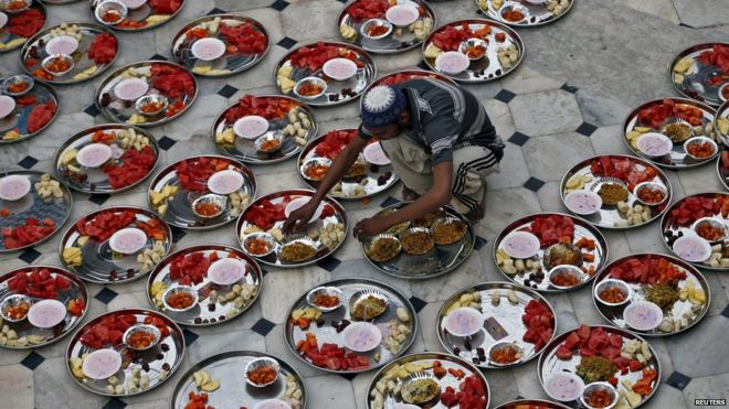 A Muslim man prepares plates of food for an Iftar meal inside a mosque during Ramadan in Ahmedabad, India