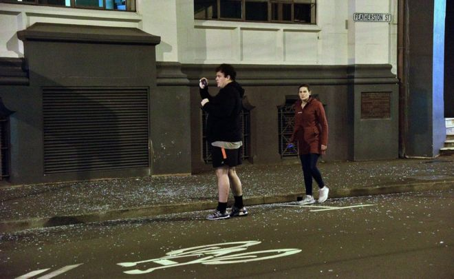 Una pareja en Wellington, tras el terremoto. En la calle se ven cristales rotos.