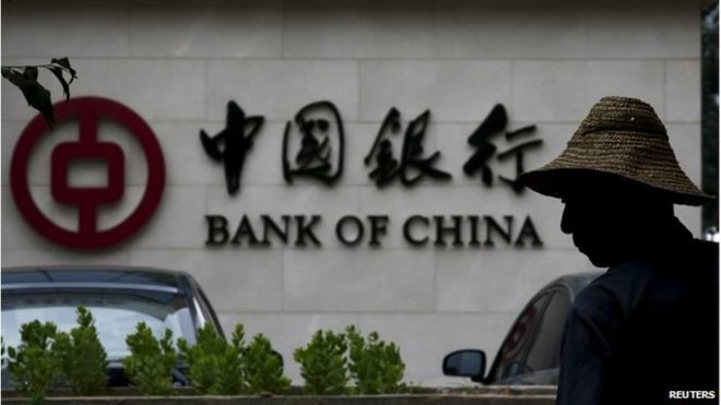 "A man is silhouetted in front of a Bank of China""s logo at its branch office in Beijing, in this July 14, 2014 file photo"