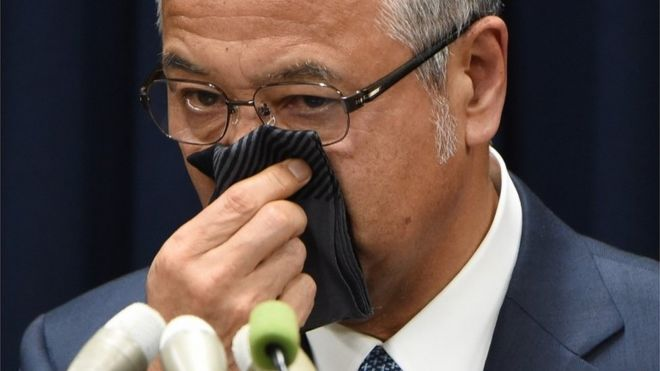 "Japan""s Economy Minister Akira Amari wipes his nose during a press conference in Tokyo on January 28, 2016."